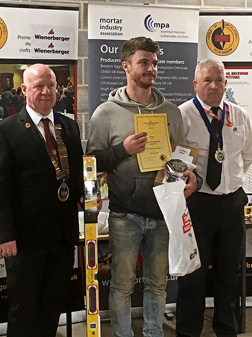 Junior winner 2019 - Junior section winner, Tom Taylor, Wiltshire College, receives his awards from president of the Guild of Bricklayers, Kevin Harold (left) and chair of the guild�s north west section, Jeff Dunn