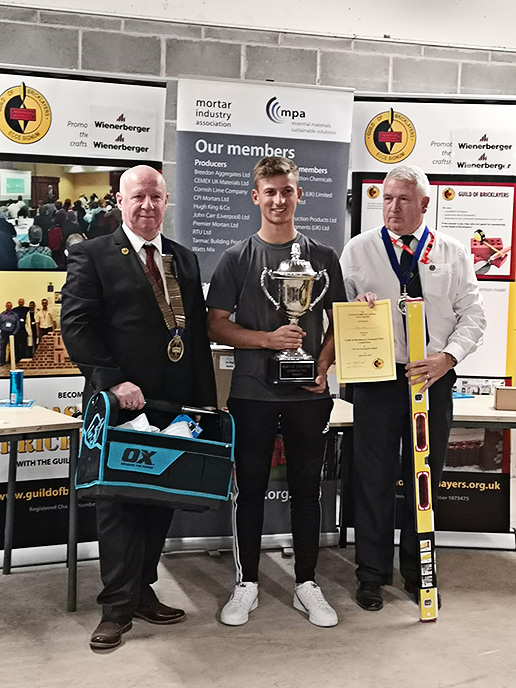 Senior winner 2019 - President of the Guild of Bricklayers, Kevin Harold (left) and chair of the guild�s north west section, Jeff Dunn, present senior winner, Adam Batty of Barnsley College with his awards