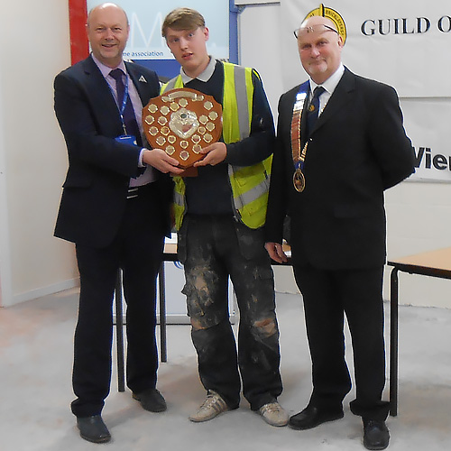 Kevin Burke, head of division, Preston College (left) and James Howe, president of the Guild Of Bricklayers (right), present Joe Higginson with his senior winner's shield.