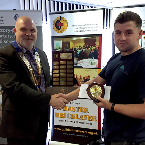 Guild of Bricklayers president, Phil Vine-Roberts, presents the award to Wales competition senior winner, Sean Howells from Bridgend College