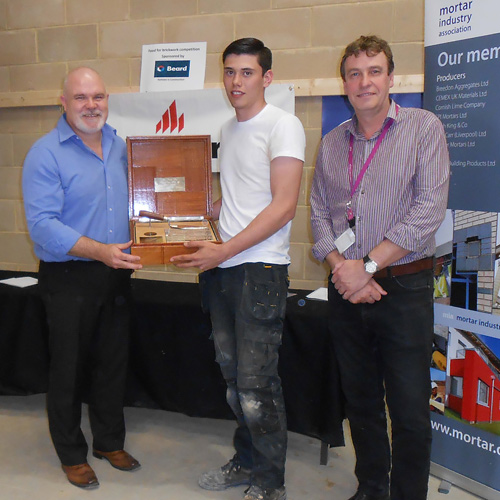 Guild of Bricklayers president, Phil Vine-Roberts (left) and the Brooklands College head of construction, Neil Houldey present the junior heat award to Tiyler Pearce of Brooklands College