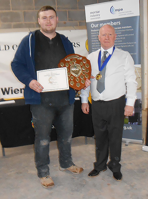 Winner of the senior section of the Guild of Bricklayers north west regional competition, Jordan Ireland, receives his awards from guild vice president, Kevin Harold.