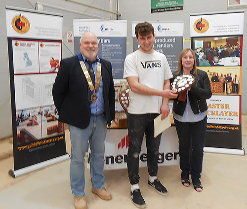 President of the Guild of Bricklayers, Phil Vine Roberts and Veronica Diett, present the junior category award to James Roberts of Northbrook College.