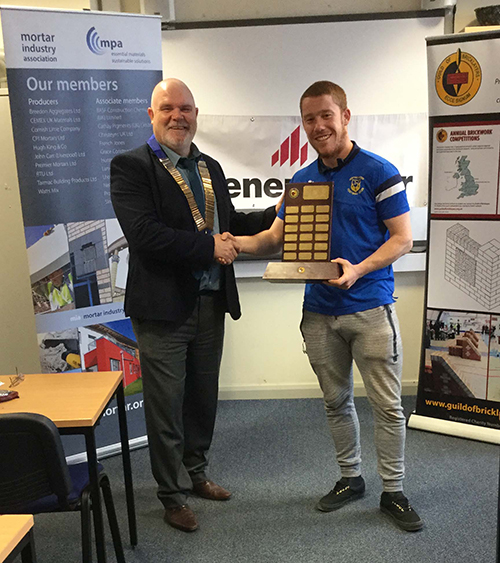 Liam McGinley of the NPTC Group, Neath, receives his senior category trophy from the president of the Guild of Bricklayers, Phil Vine Roberts.