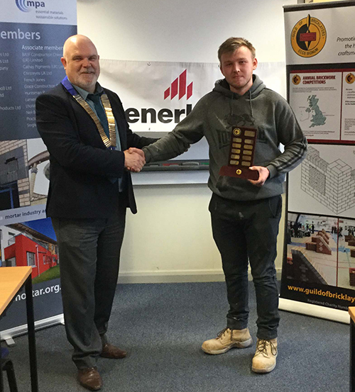 President of the Guild of Bricklayers, Phil Vine Roberts, presents Matthew Lloyd Hughes,Coleg Menai, with his trophy as winner of the junior section.