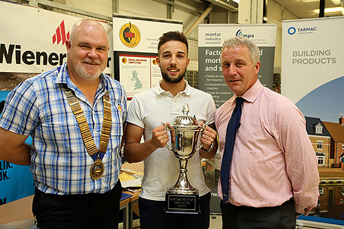 Tyler Pearce of Brooklands College receives the MIA cup for winning the senior section of the Guild of Bricklayers national 2017 competition from guild president, Phil Vine Roberts ( left) and Tarmac Building Products' Iain Betts.