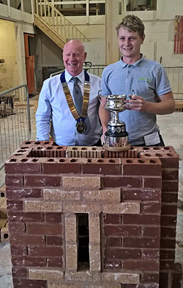 Notts/Lincoln heat senior winner, William Johnson, receives his cup from Guild of Bricklayers president, Kevin Harold