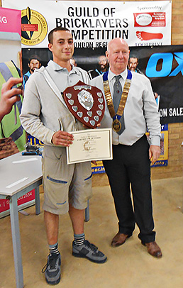 Guild of Bricklayers president, Kevin Harold, presents the London heat junior section winner's shield to Zak Kharbough